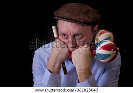 Portrait of sad mature musician with Ukrainian woodwind instrument sopilka and maracas - stock photo