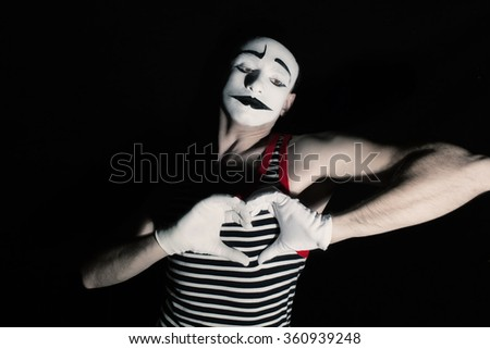 Portrait of sad mime with heart on black background - stock photo