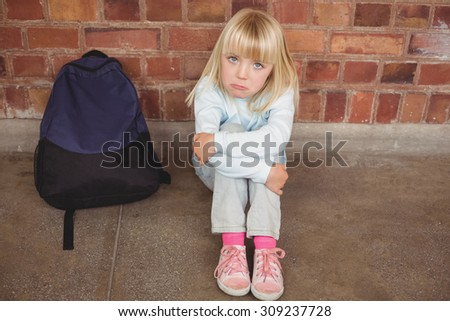 Portrait of sad pupil sitting alone on ground at corridor - stock photo