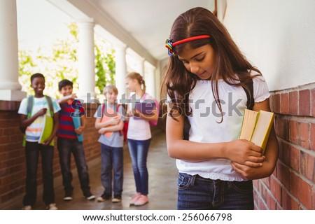 Portrait of sad schoolgirl with friends in background at school corridor - stock photo