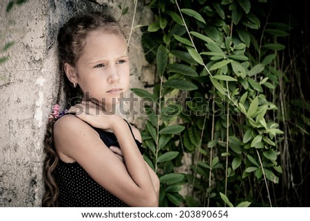 Portrait of sad teen girl standing near stone wall at the day time - stock photo