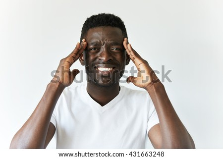 Portrait of sad unhappy African man having bad headache, looking at the camera with painful expression, holding hands on his temples. Human face expressions, emotions and feelings. Body language - stock photo