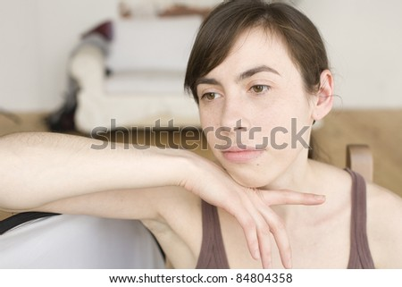 portrait of sad young woman sitting at home