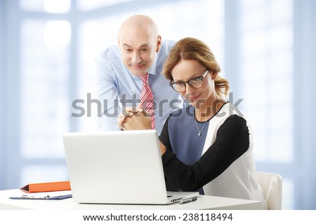 Portrait of sales people working on presentation while sitting at office. Teamwork. - stock photo