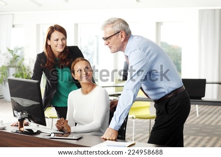 Portrait of sales team working together on laptop at office.  - stock photo