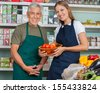 Portrait of saleswoman holding vegetable basket with male colleague in grocery store - stock photo