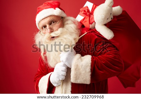 Portrait of Santa carrying huge red sack with xmas gifts for kids - stock photo