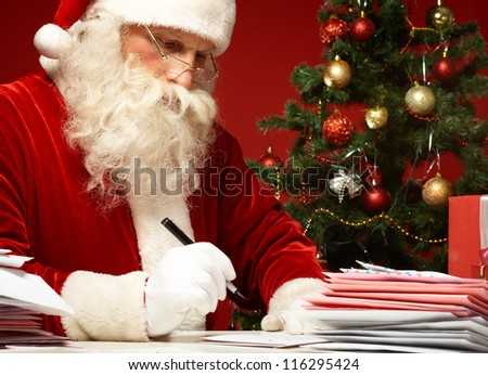 Portrait of Santa Claus answering Christmas letters - stock photo