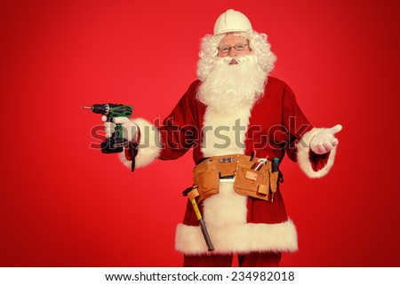 Portrait of Santa Claus - builder in helmet builder holding construction tools over red background.  - stock photo