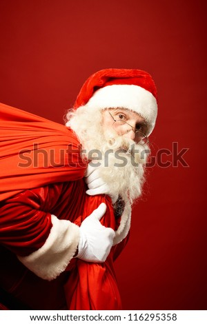 Portrait of Santa Claus carrying huge red sack and looking at camera