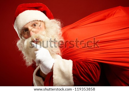 Portrait of Santa Claus carrying huge red sack and showing gesture of silence - stock photo