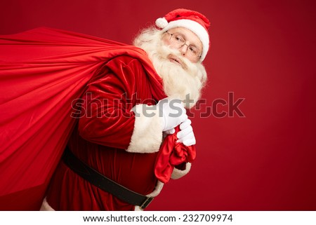 Portrait of Santa Claus carrying huge red sack with xmas gifts - stock photo