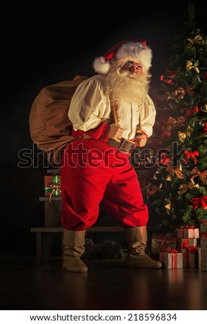 Portrait of Santa Claus carrying huge sack with presents indoor at home near Christmas tree - stock photo