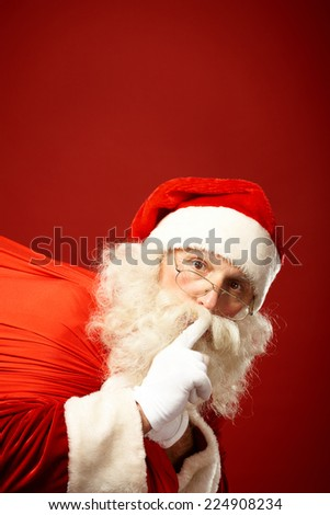 Portrait of Santa Claus carrying sack and keeping forefinger by his mouth - stock photo