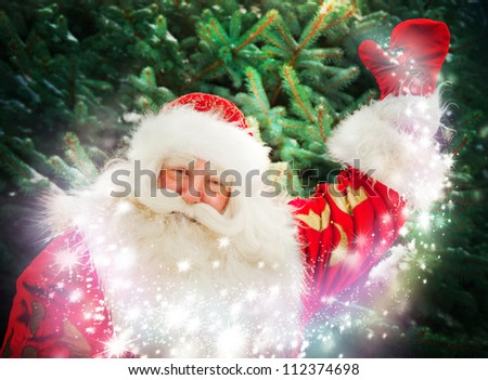 Portrait of Santa Claus conjuring against christmas tree - stock photo
