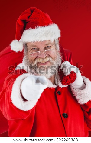 Portrait of Santa Claus holding Christmas bag and gesturing against red snowflake background