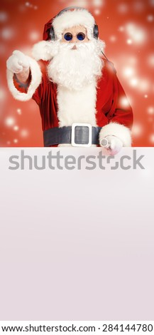 Portrait of Santa Claus in headphones singing with microphone. He is holding white billboard. Christmas. - stock photo