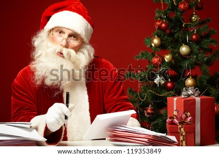 Portrait of Santa Claus looking at camera while answering Christmas letters