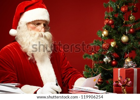 Portrait of Santa Claus looking at envelope in his hands - stock photo