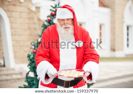 Portrait of Santa Claus offering cookies outside house - stock photo