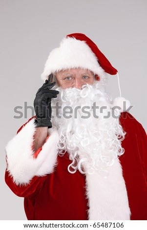 Portrait of Santa Claus on the phone, looking at camera, isolated on gray background.? - stock photo