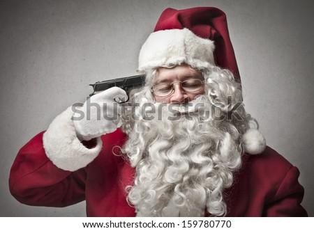 portrait of Santa Claus pointing a gun on his head - stock photo