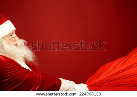 Portrait of Santa Claus pulling big red sack with gifts