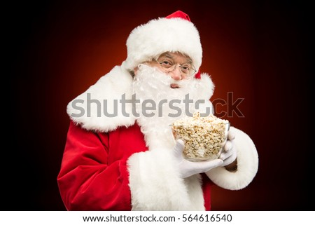 Portrait of Santa Claus showing full bowl of popcorn on dark