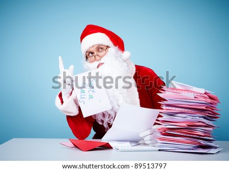 Portrait of Santa Claus sitting with raised forefinger in front of heap of letters