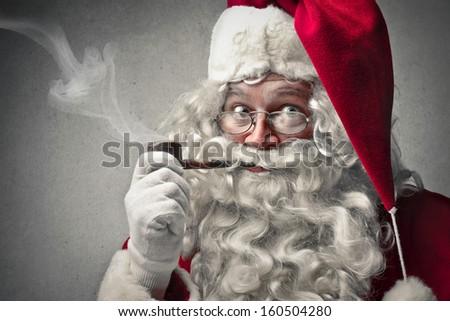 portrait of Santa Claus smokes a pipe - stock photo