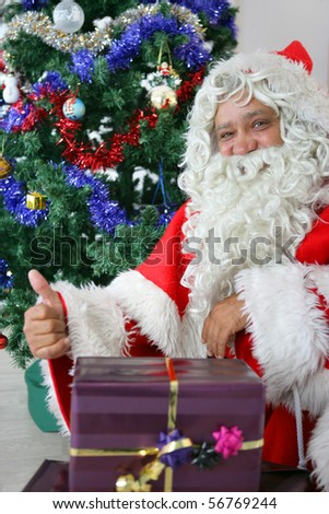 Portrait of Santa Claus with a thumb raised near a Christmas tree