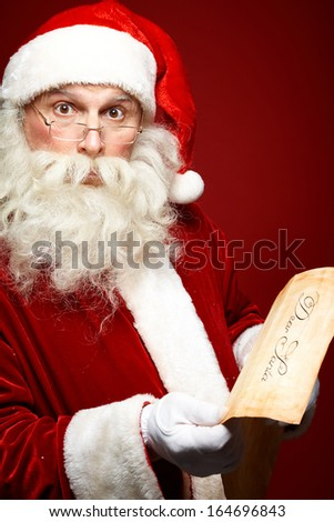 Portrait of Santa Claus with Christmas letter in his hands looking at camera astonishingly