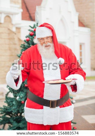 Portrait of Santa Claus with cookies and milk standing against house - stock photo