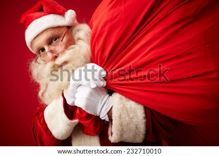 Portrait of Santa Claus with huge and heavy red sack looking at camera - stock photo