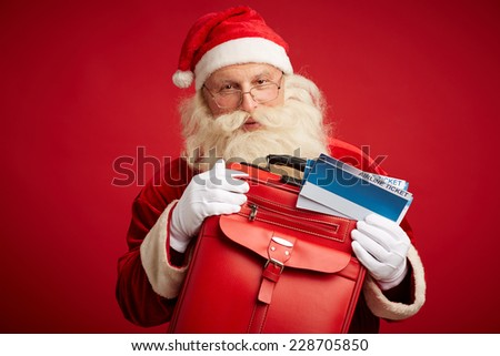 Portrait of Santa Claus with red leather suitcase and airline tickets looking at camera - stock photo