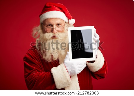 Portrait of Santa Claus with touchscreen looking at camera