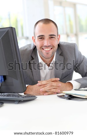 Portrait of satisfied businessman in office - stock photo