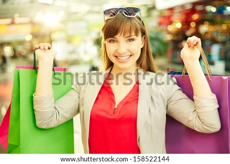 Portrait of satisfied girl holding colorful shopping bags - stock photo