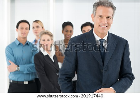 Portrait Of Satisfied Mature Businessman With His Team