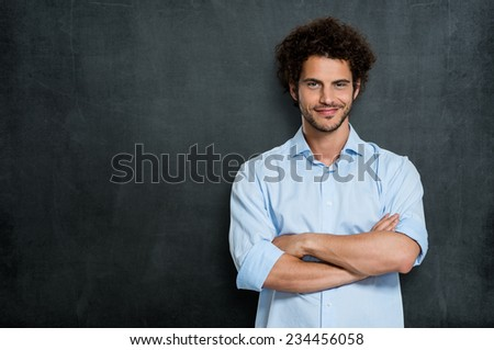 Portrait Of Satisfied Young Man Over Gray Background - stock photo