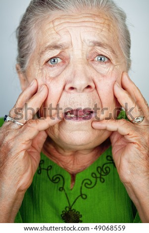 Portrait of scared and worried senior wrinkled lady - stock photo