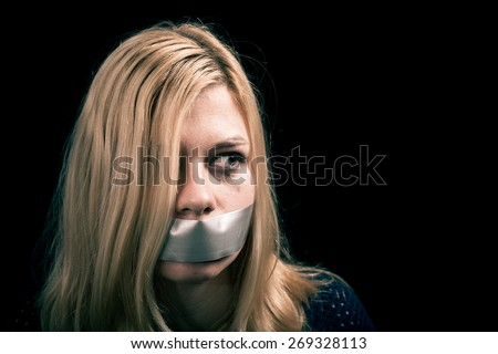 Portrait of scared kidnapped woman hostage with tape over her mouth