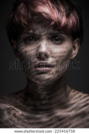 Portrait of scared or frightened girl with writing and erased text on her body - stock photo