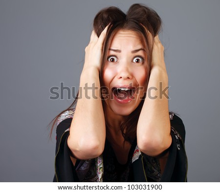 portrait of scared woman against dark background - stock photo
