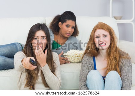 Portrait of scared young female friends with remote control and popcorn bowl on sofa at home - stock photo