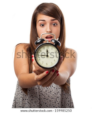 portrait of scared young woman holding an alarm clock isolated on white