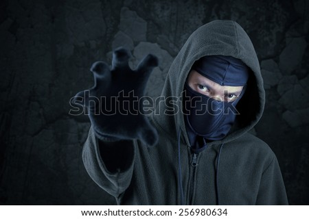 Portrait of scary bandit with mask and hoodie try to take something - stock photo