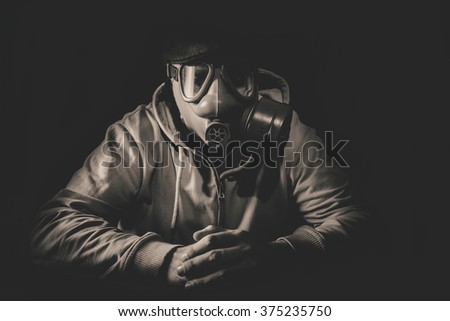 Portrait of scary man with gas mask, low key and monochrome - stock photo