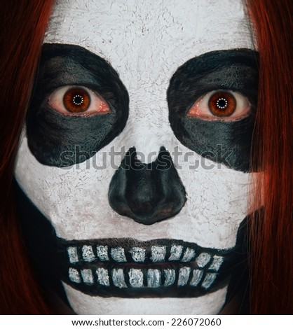 Portrait of scary skull woman with Halloween makeup and red hair