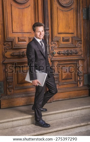 Portrait of School Boy. Dressing formally in black suit, necktie, white shirt, carrying laptop computer, a young college student walking down stairs form vintage style office door way on campus, smile - stock photo